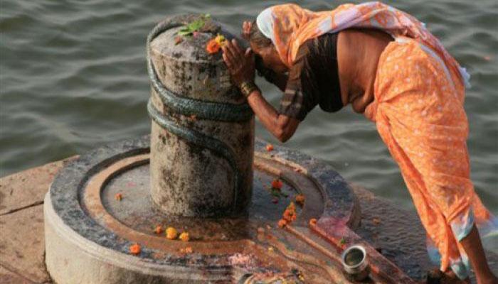 Creyente adorando al Shiva Lingam